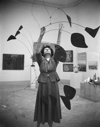 """Peggy Guggenheim with Alexander Calder's """"Arc of Petals"""" at the Greek Pavilion, 24th Venice Biennale, 1948. © Fondazione Solomon R. Guggenheim, foto Archivio CameraphotoEpoche, donazione Cassa di Risparmio di Venezia, 2005."""